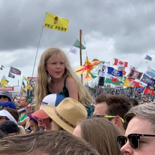 photo of little girl with music festival flags at new orleans jazz festival 50th anniversary for blog on music festival survival by beth nault-warner